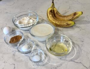 A close up image of the 8 ingredients used to make the banana pancakes